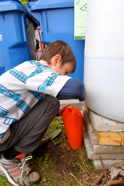Jeune homme remplissant un arrosoir.